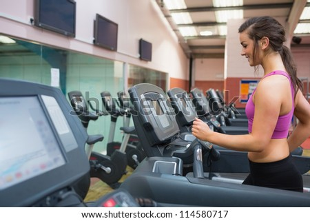 Woman running and training on a treadmill in a gym wearing black shorts and purple top - stock photo