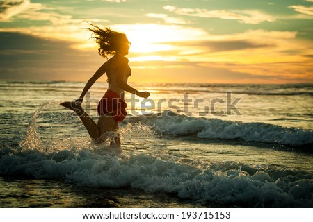woman running at the beach in the dawn time - stock photo