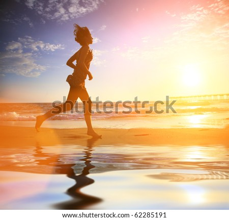 Woman running by the ocean beach at sunset - stock photo