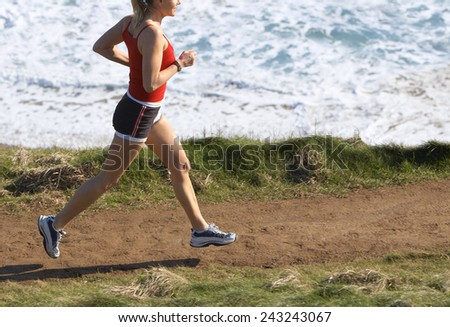 woman running down a path at the beach - stock photo