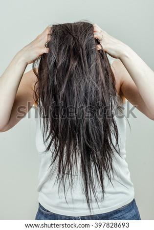 Woman running her fingers through her hair scratching her scalp. Portrait. - stock photo
