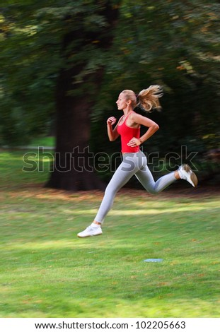 Woman running in a park - stock photo