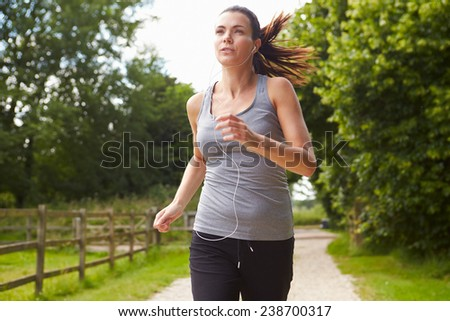 Woman Running In Countryside Wearing Earphones - stock photo