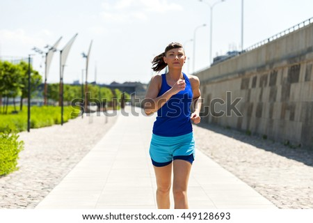 Woman running in the city park. - stock photo