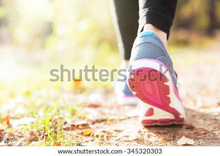 Woman running legs in sunset forest - stock photo