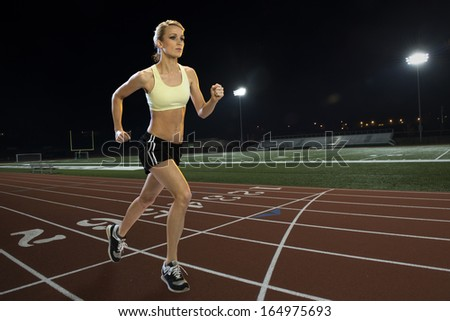 Woman running on a track at night - stock photo