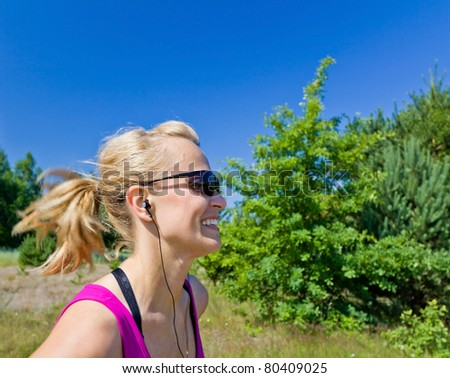 Woman running on country road in summer nature, blurred motion - stock photo