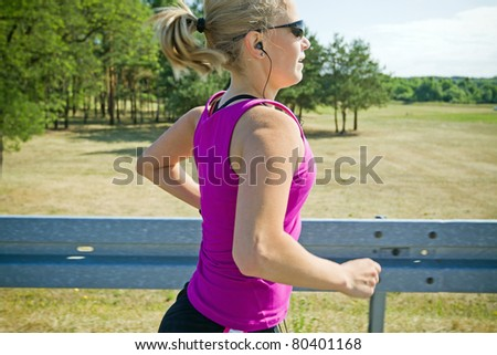 Woman running on country road in summer nature, motion blur - stock photo
