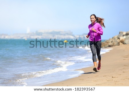 Woman running on San Francisco beach with Alcatraz in background. Smiling happy female athlete runner training on waterfront in San Francisco, California, USA. Mixed race fit fitness sport model. - stock photo