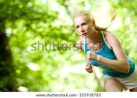 Woman Running Outdoors in Forest - stock photo