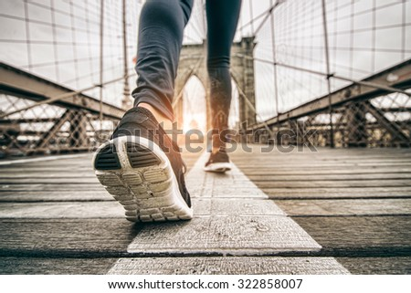 Woman running outdoors - Young sportive girl jogging at sunset on Brooklyn Bridge, close up on shoes - stock photo
