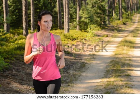 Woman running through forest outdoor training on sunny day - stock photo