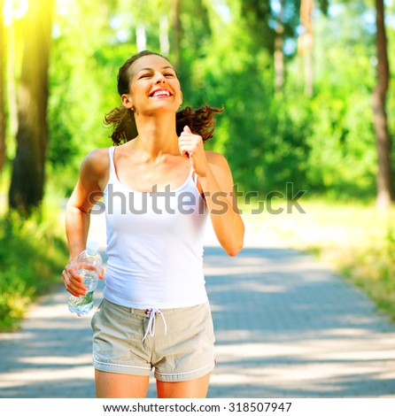 Woman running with bottle of water. Young sporty lady jogging outdoor in the park. Brunette model enjoy the training Workout. Exercises. Healthy lifestyle.  - stock photo