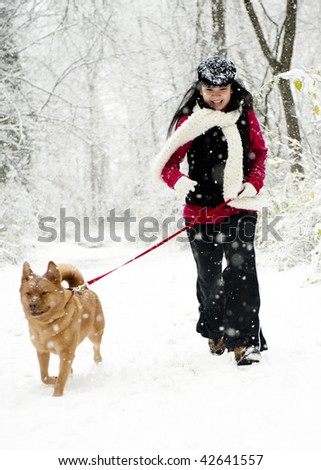 Woman running with dog during snow fall - stock photo