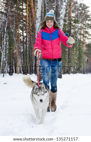 Woman running with dog in winter nature - stock photo