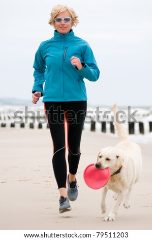Woman running with dog on the beach - stock photo