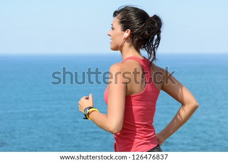 Woman running with earphones on sea background. Caucasian beautiful fitness girl working out on summer. Copyspace. - stock photo