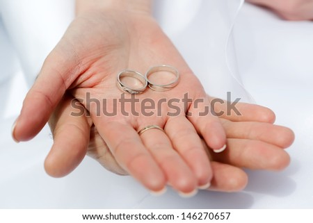 Woman's and man's wedding hands with the rings, focused to the rings - stock photo