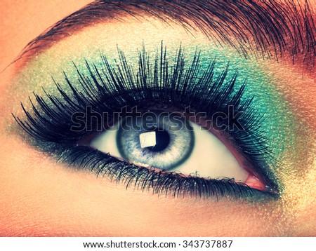 Woman's eye with green eye make-up. Long eyelashes - stock photo