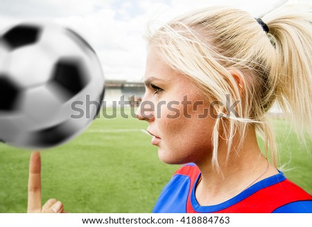 woman's face against green grass field, sky and stadium. football girl wear uniform and turn on finger white and black ball.  - stock photo