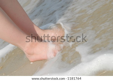 Woman's feet covered by a wave - stock photo