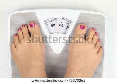 Woman's feet on bathroom scale - stock photo