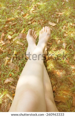 Woman's feet on  grass.  Relaxation concept. Color filter background and vintage style. - stock photo