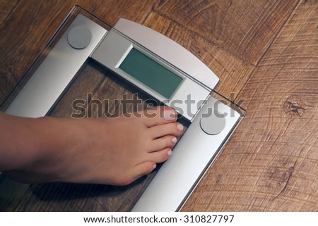Woman's feet stepping on weight scale. Close-up of woman's foot on bathroom scale. Dieting concept. - stock photo