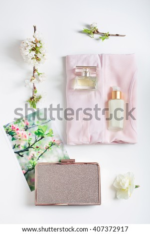 Woman's female summer clothing and accessories: top, face cream, perfume, clutch, photo of and fresh flowers on white background, top view. Modern looks, new season holiday, evening fashion concepts. - stock photo