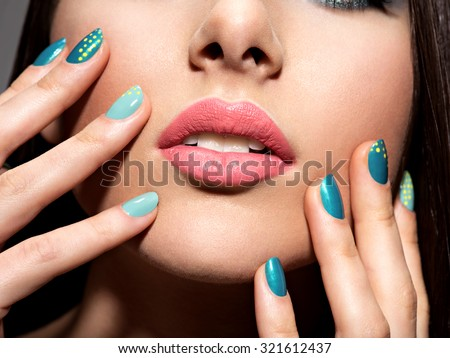 Woman's fingers with motton blue color of the nails on the face - stock photo