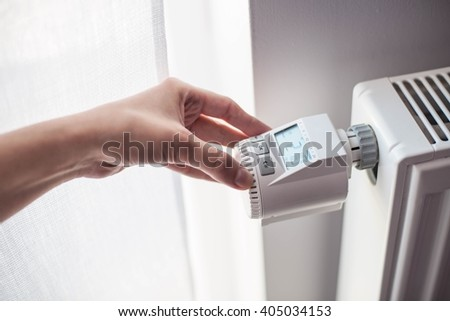 Woman's hand adjusting temperature on home wall heater - stock photo