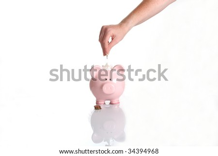 woman's hand dropping a coin piggy bank - stock photo