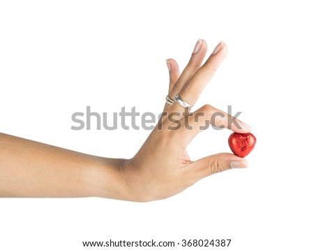 Woman's hand giving heart shape chocolate. Isolated with clipping path. - stock photo