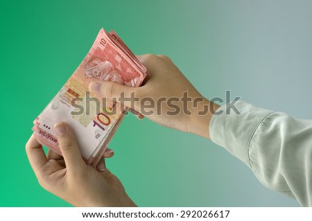 woman's hand hold some malaysia currency ten ringgit - stock photo