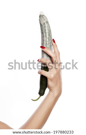woman's hand holding a cucumber with a condom - stock photo