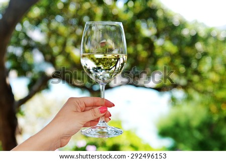woman's hand holding  glass of white wine - stock photo