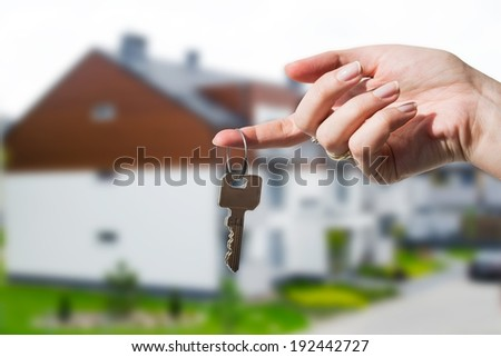 Woman's hand holding keys to new house - stock photo