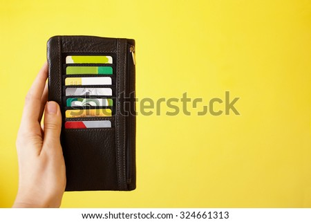 Woman's hand holding leather wallet with colorful credit cards. Savings concept - stock photo