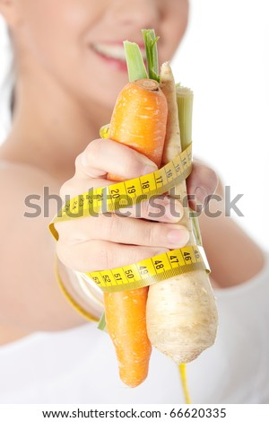 Woman's hand holding vegetables and measuring tape, isolated on white. Diet concept - stock photo