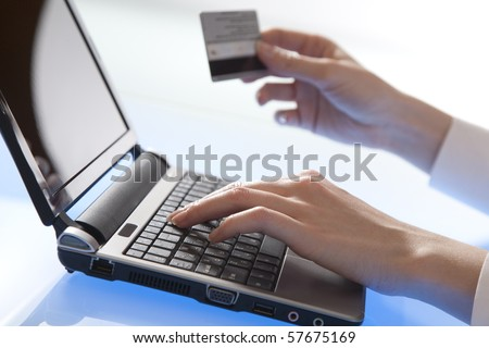 Woman's hand holds a credit card while entering data in laptop - stock photo