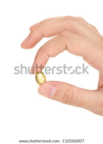 woman's hand holds a pellets of fish oil on white background close-up - stock photo