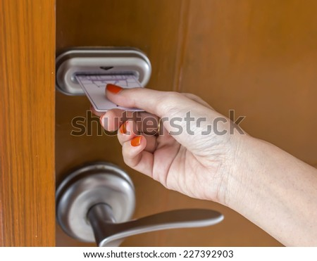 woman's hand inserting key card in an electronic lock - stock photo