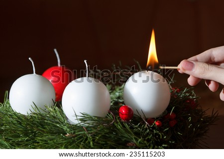 woman's hand lit the first candle of the Advent wreath - stock photo