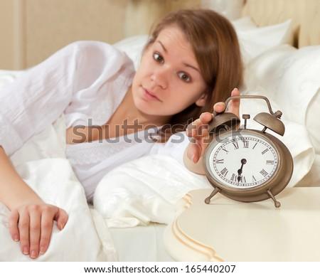 Woman's hand off the alarm clock, 6.30 am - stock photo