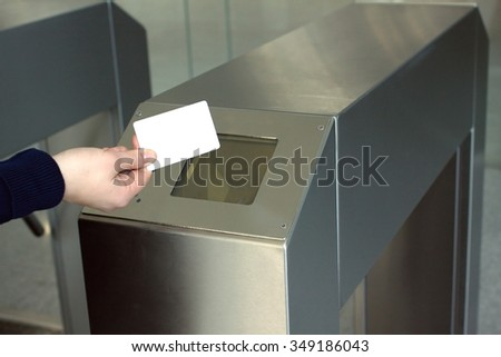 Woman's hand puts white plastic card indoor to electronic reader access control system. Closeup view - stock photo