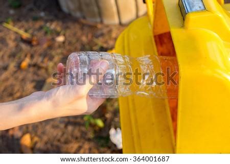 Woman's hand putting a plastic bottle in trash bin - stock photo