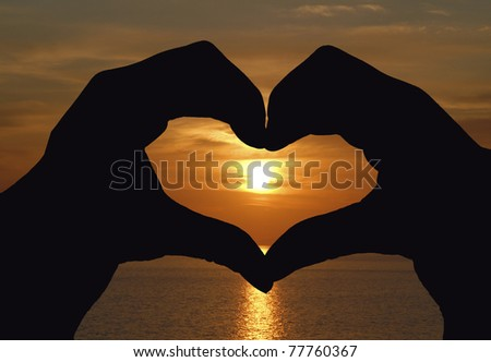 Woman's hand united forming a heart shape symbol at sunset - stock photo