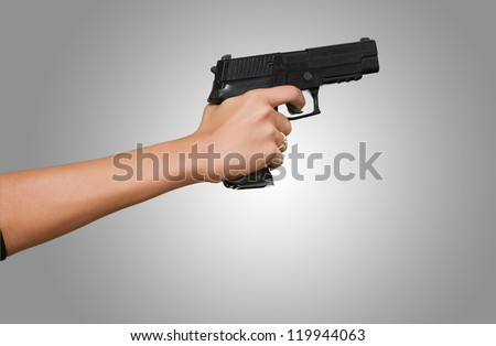 Woman's Hand With A Gun against a grey background - stock photo