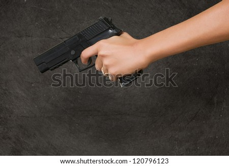 Woman's Hand With A Gun against a grunge background - stock photo