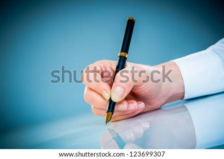 Woman's hand with a pen on a blue background - stock photo